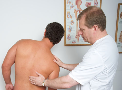 Osteopath looking at someone's back
